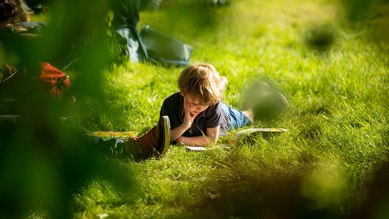 Boy reading on Hay Festival site