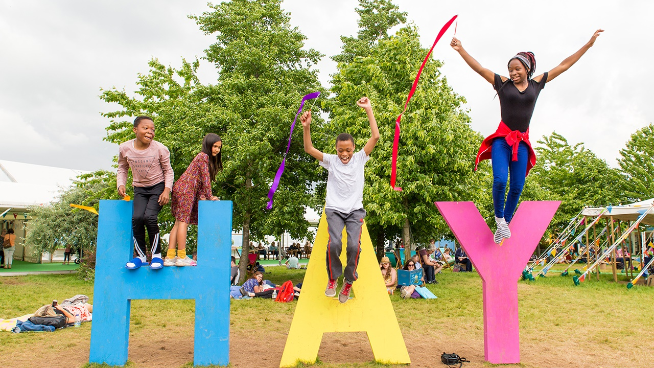 Young people having fun on Hay Festival sign