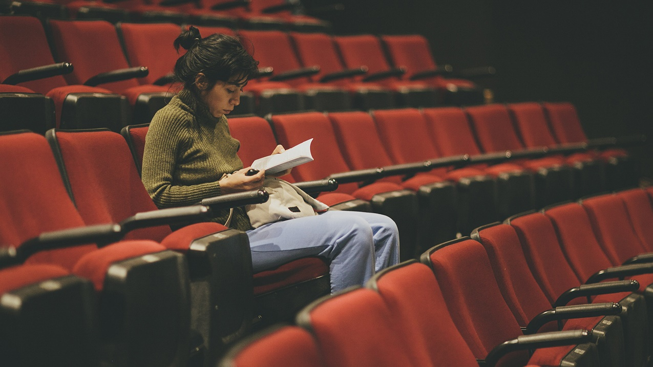 Woman reading in empty auditorium