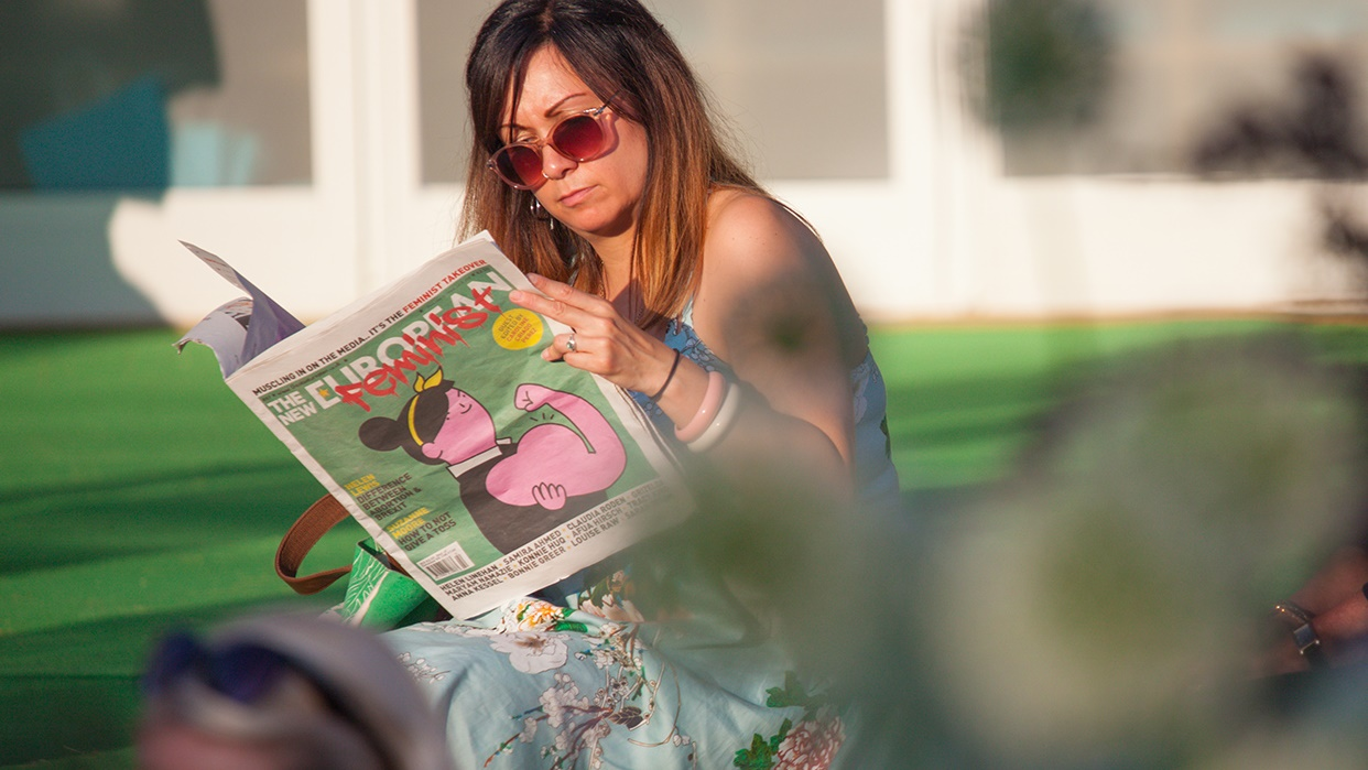 Woman reading newspaper in sunshine