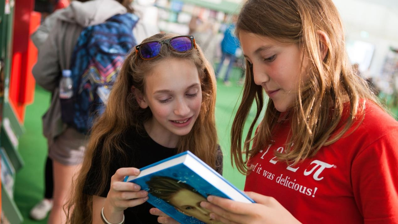Girls sharing book in Hay Festival bookshop