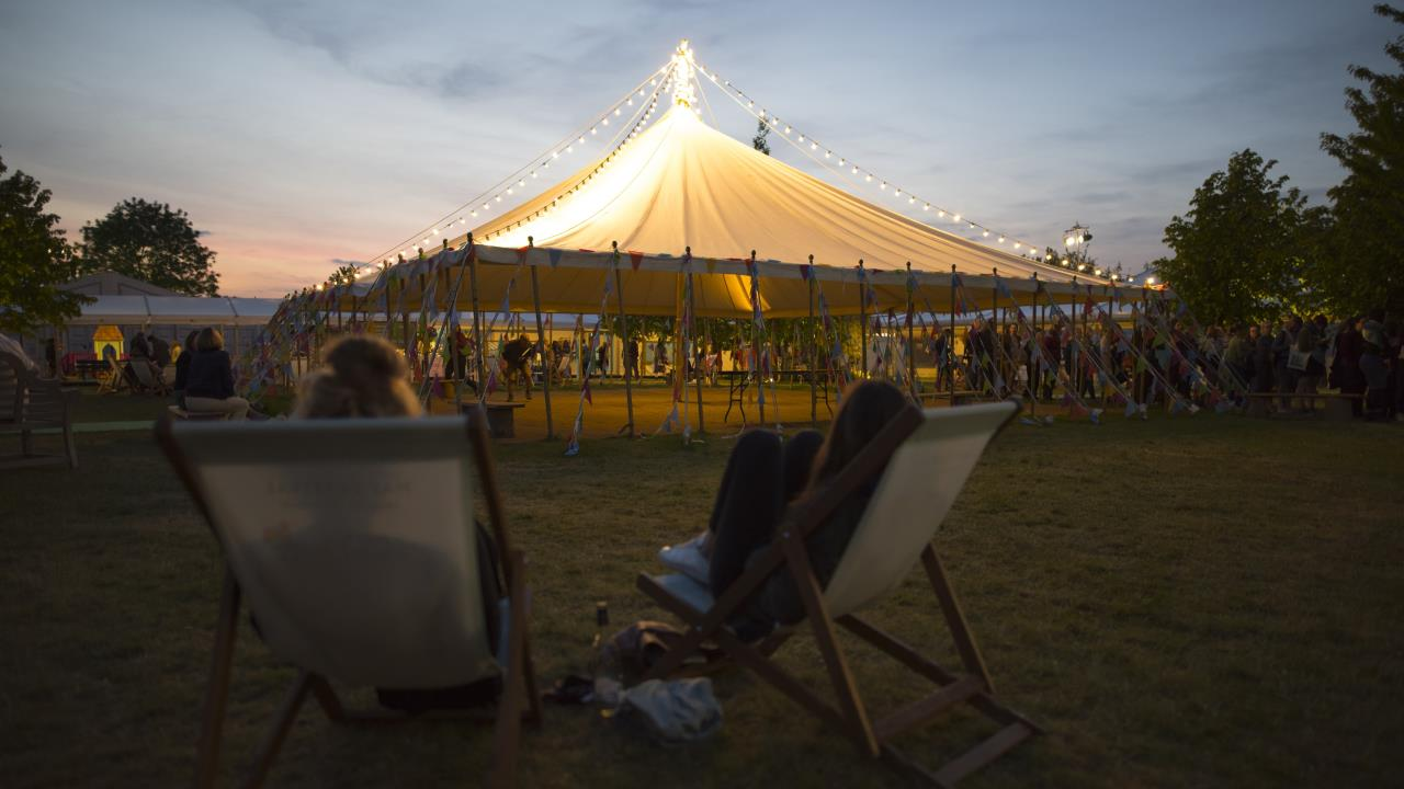 Hay Festival tent lit up at twilight