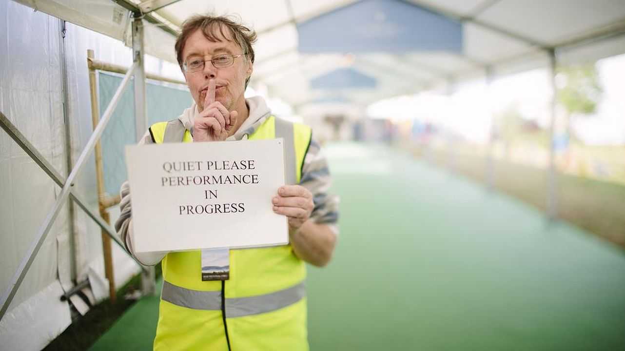 Hay Festival Steward holding a Quiet Please sign