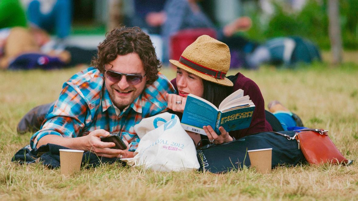 Couple lying on floor reading at Hay Festival