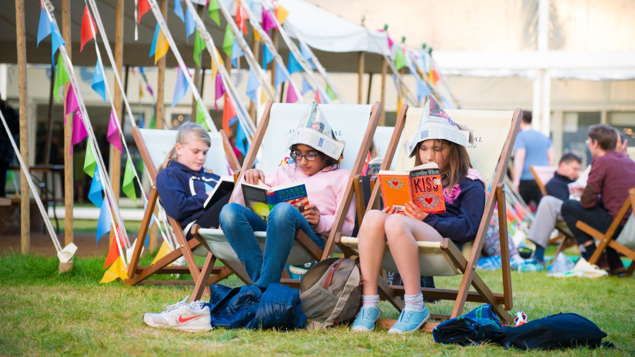 Girls reading in deckchairs at Hay